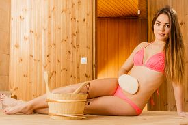 image of sauna woman  - Young woman in wood finnish spa sauna massaging skin with exfoliating glove - JPG