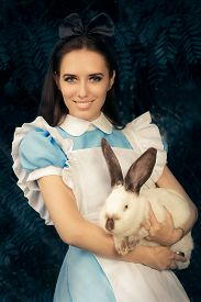 stock photo of bunny costume  - Portrait of a smiling girl in a blue costume holding a white bunny - JPG