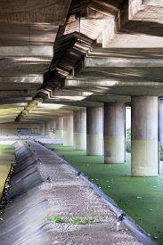 stock photo of green algae  - Pillars in green algae water under an elevated road - JPG