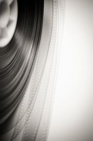 stock photo of mm  - 35 mm film detail with movie reel in black and white  - JPG