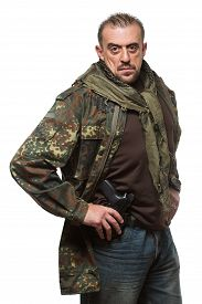 stock photo of terrorist  - Male terrorist in a military jacket with a gun in his hand - JPG