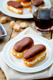 foto of eclairs  - eclairs with cheese cream and chocolate glaze on a dark wood background - JPG