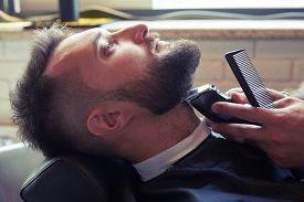 picture of barber razor  - sideview portrait of handsome man in professional barbershop - JPG