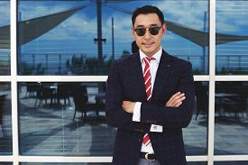 stock photo of half-dressed  - Half length portrait of smiling Asian businessman dressed in trendy clothes standing with crossed arms outdoors - JPG