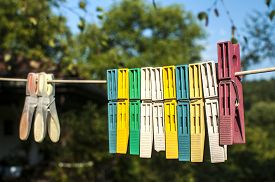 picture of clotheslines  - Colored plastic clothesline laundry clips hanging on rope - JPG