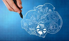 picture of mechanical drawing  - Person hand drawing cogwheels mechanism on blue background - JPG