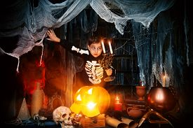 stock photo of boys night out  - Scary funny boy in a costume of skeleton in a wizarding lair - JPG