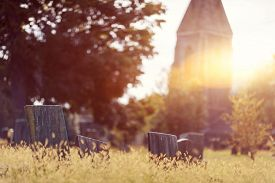 stock photo of tombstone  - Tombstone and graves in a church graveyard in the fall - JPG