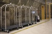 Three luggage carts with wheels near wall in hall in modern hotel poster