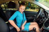 Girl In Dress In Car Seat Belt For Safety Before Driving, Side View. Beautiful Young Woman In Car Fa poster