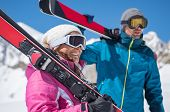Happy couple on ski holiday in snowy mountains. Smiling young couple with ski on shoulder standing o poster