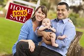 stock photo of mixed race  - Happy Mixed Race Couple with Baby in Front of Sold Real Estate Sign - JPG