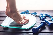 Female Feet Standing On Electronic Scales, Dumbbells And Measuring Tape. Concept Of Slimming And Wei poster