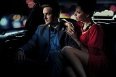 stock photo of limousine  - Colorful image of beautiful couple sitting in a limousine - JPG