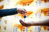 Concept Of Buying, Selling And Renting Housing. A Womans Hand Passes The Keys To The Mans Hand Fro poster