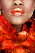 african young woman with orange feathers and orange full lips