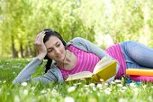 Girl Lying On Grass In Park With Book And Headset