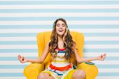 Joyful Long-haired Girl Meditating While Sitting In A Lotus Pose On Blue Striped Background. Pretty  poster