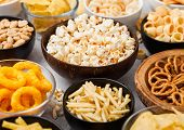 All Classic Potato Snacks With Peanuts, Popcorn And Onion Rings And Salted Pretzels In Bowl Plates O poster