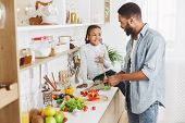 Cute Afro Kid Girl And Her Dad Cooking In Kitchen At Home. Happy Family Cooking Concept poster