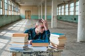 Photo Of A Student Having Difficulty While Studying For The Exam. Stack Of Books In Front Of Him On  poster