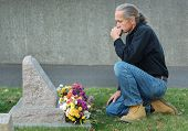 image of grieving  - Man sitting at gravesite with a look of sadness - JPG