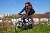 stock photo of sakhalin  - Man on bicycle on background of city - JPG