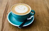 A Cup Of Cappuccino With Latte Art And Spoon On Wooden Background. Beautiful Foam, Greenery Ceramic  poster