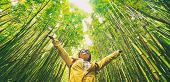 Sustainable eco-friendly travel tourist hiker walking in natural bamboo forest happy with arms up in poster