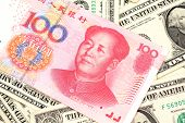 A Red One Hundred Chinese Yuan Bank Note Close Up In Macro With American One Dollar Bills poster