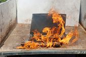 Computer Fire. A laptop computer engulfed in flames of hot fire. Smoke and Fire burn and melt a comp poster