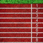 stock photo of track field  - red running tracks with white start numbers at stadium closeup - JPG
