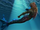 stock photo of fable  - Ocean light illuminates a magical mermaid as she swims up to the ocean surface - JPG