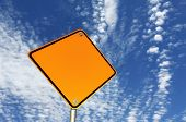 picture of road sign  - Blank yellow road sign against brilliant blue sky with scattered clouds - JPG
