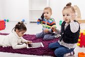 stock photo of toy phone  - Cute little kids playing in the room with mobile phones and tablet - JPG