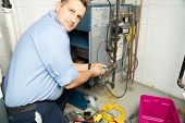 stock photo of plumber  - Plumber fixing gas furnace using electric and plumbing tools - JPG