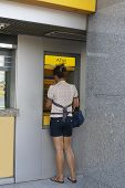 image of automatic teller machine  - A woman using cash machine - JPG