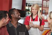 pic of patron  - Teenage waitress taking orders from smiling patrons in cafe - JPG