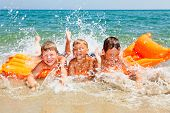 picture of children beach  - Three kids splashing water on a beach - JPG