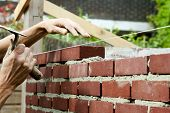 pic of bricklayer  - Bricklayer with trowel in hand building a wall - JPG