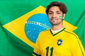 Portrait of confident young sports fan standing against Brazilian flag