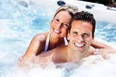stock photo of sauna woman  - Happy couple relaxing in hot tub - JPG