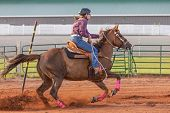 pic of barrel racer  - Young woman competing in a pole bending equestrian competition - JPG