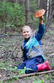 picture of face-fungus  - The joyful boy in wood holds in a hand the big aspen mushroom which it has found - JPG