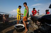 PADANG - AUGUST 25: Fishmongers negotiate fish price and trade at an outdoor village market in Padan