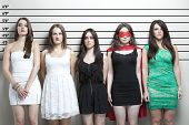 image of lineup  - Young woman in superhero costume with friends in a police lineup - JPG