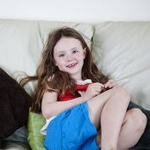 picture of settee  - Pretty young girl relaxes on comfy settee - JPG