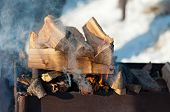 picture of inflamed  - inflames smoking logs in the grill outdoors - JPG