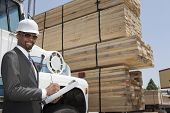picture of take responsibility  - Portrait of African American male contractor writing notes while standing by logging truck - JPG