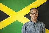 picture of jamaican flag  - Portrait of a man with raised eyebrows against Jamaican flag - JPG